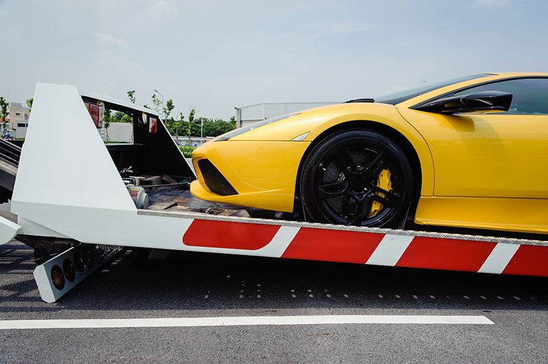 Yellow sports car on towing bed