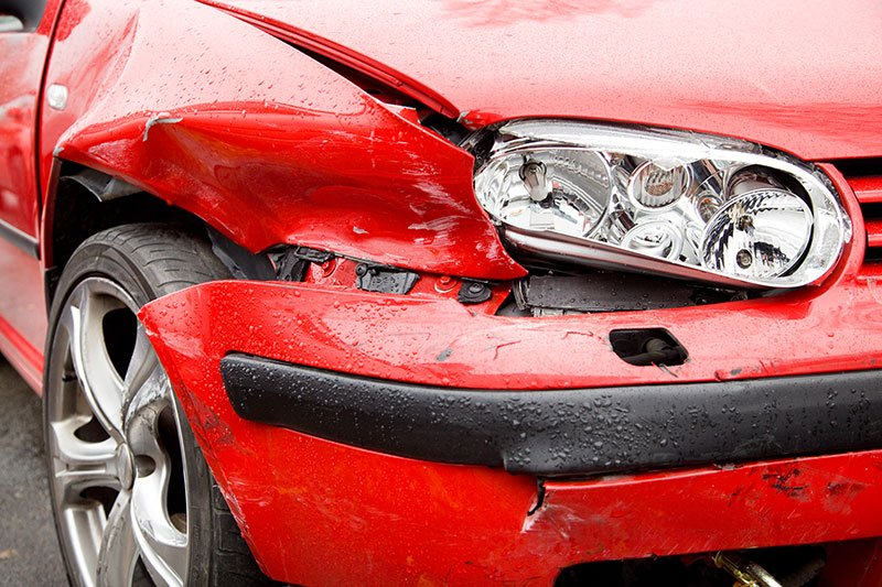 Smashed bumper of red car