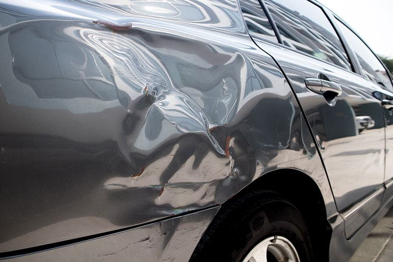 Dent in the side of a gray car
