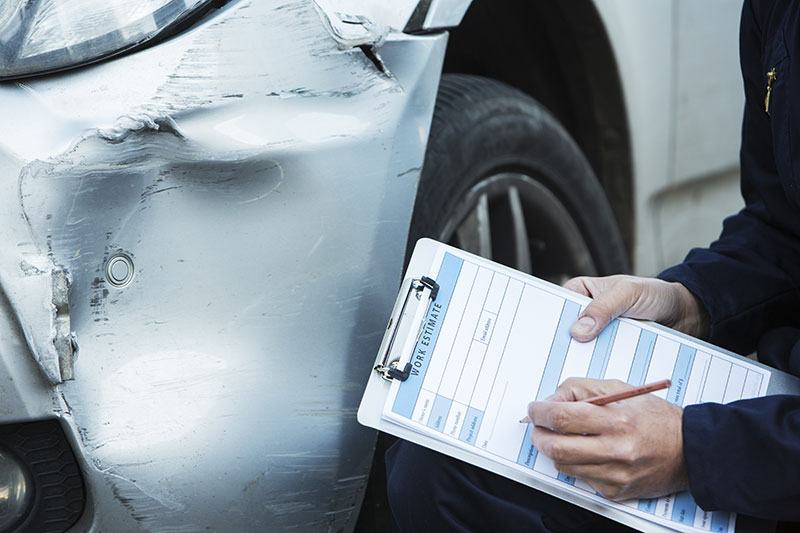 Mechanic writing up an estimate on a damaged car